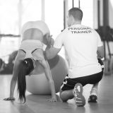 Trainer assisting and correcting woman on pilates ball during exercise
